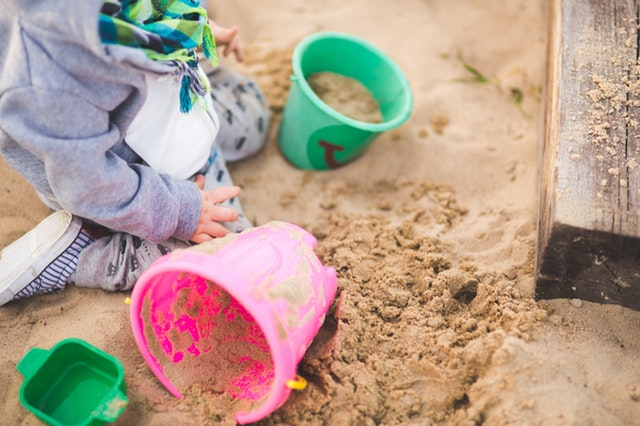 little boy digging for dinosaur egg in sand pit